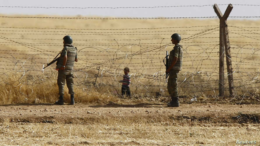 Turkish soldiers stand guard as a Syrian refugee boy waits behind the border fences to cross into Turkey on the Turkish-Syrian border, near the southeastern town of Akcakale in Sanliurfa province, Turkey, June 5, 2015.