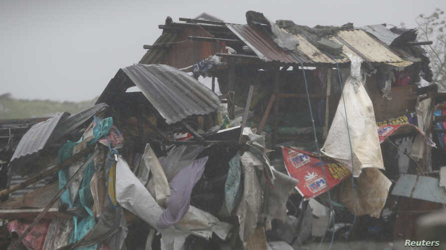 A squatter's house is pounded Typhoon Rammasun as it hit the coastal town of Bacoor, Cavite southwest of Manila, July 16, 2014.