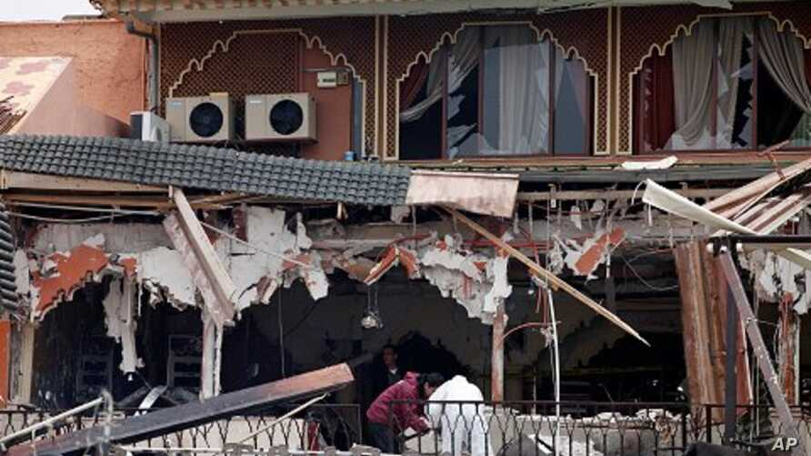 Investigators work at the site of a blast at a cafe in Marrakech, April 28, 2011