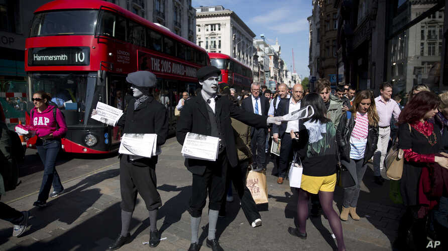 FILE - Men dressed as 1920s newspaper boys with 'greyscale