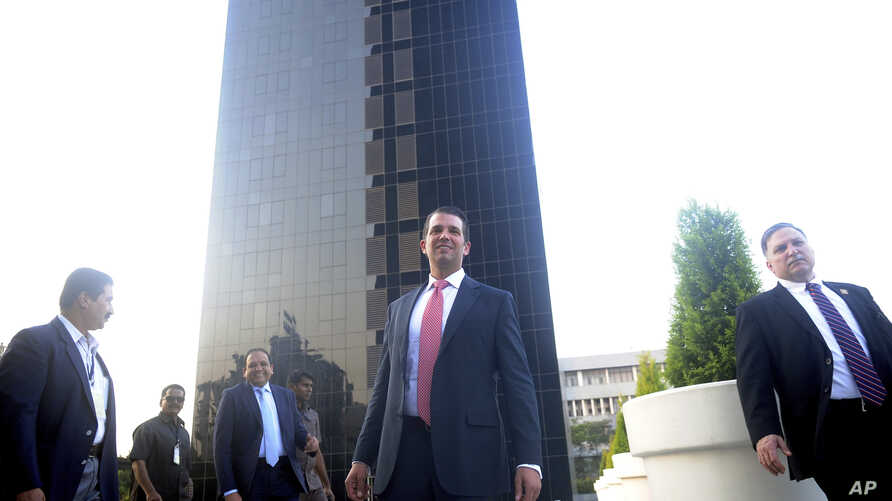 The eldest son of U.S. President Donald Trump, Donald Trump Jr., center, stands in front of Trump Towers after its inauguration in Pune, India, Feb. 21, 2018.