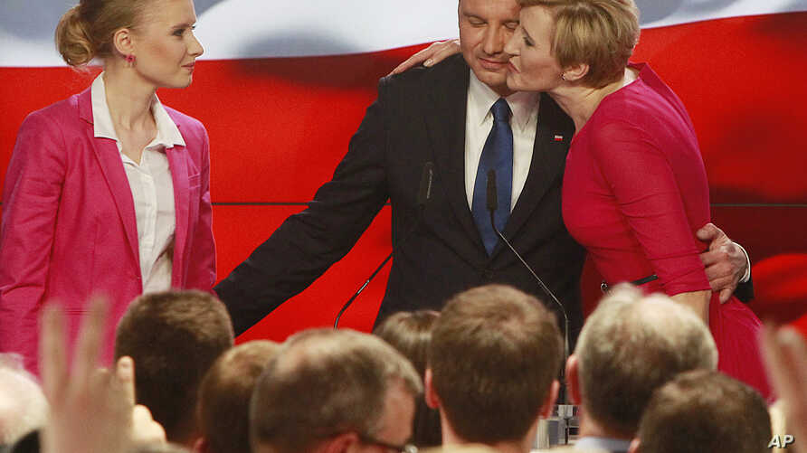 Andrzej Duda, candidate of the conservative opposition Law and Justice party, receives a kiss from his wife Agata, right, as his daughter Kinga, left, watches, after the announcement of the first exit polls in the first round of the Polish presidenti