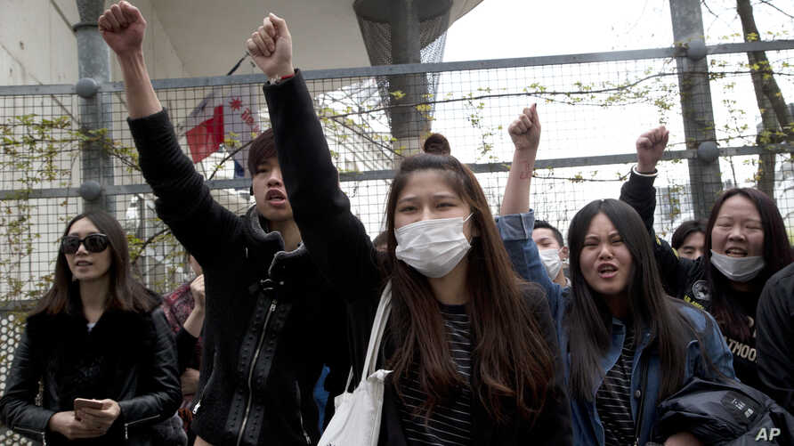 Demonstrators from the Asian community protest outside Paris' 19th district's police station, March 28, 2017.