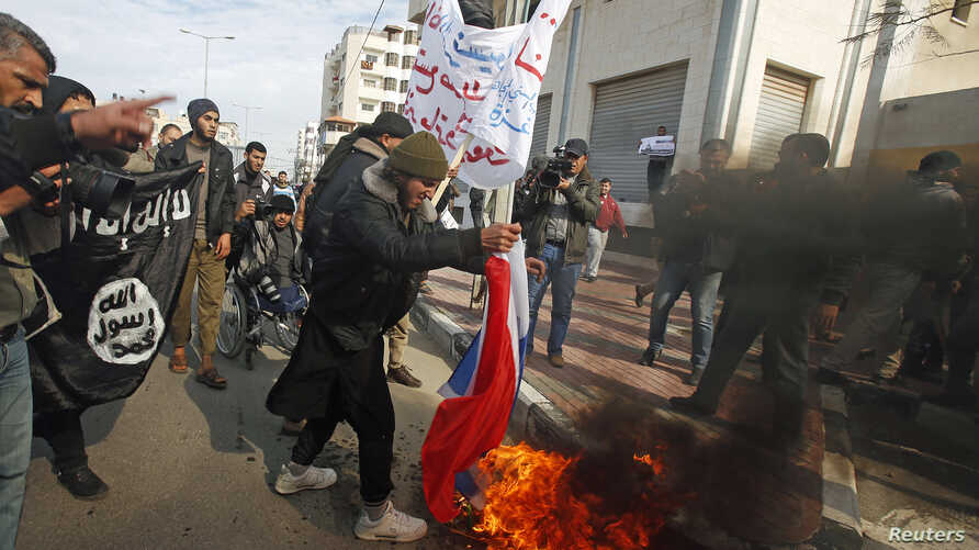 A Palestinian Salafist burns a French national flag during a protest against the satirical French weekly magazine Charlie Hebdo's cartoons of the Prophet Muhammad, outside the French Cultural Center in Gaza city January 19, 2015.