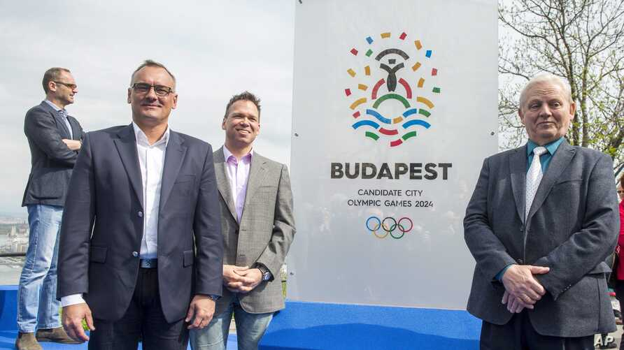 President of the Hungarian Olympic Committee Zsolt Borkai, left, Chairman of the Budapest 2024 bid Balazs Furjes, second left, and Budapest Mayor Istvan Tarlos, right, pose in front of the logo of  host city candidate Budapest for the 2024 Olympic an