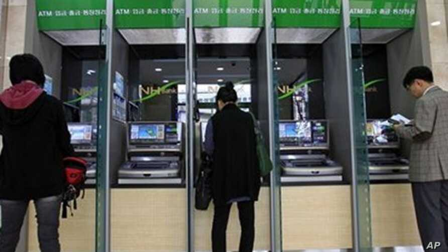 Customers use ATM machines at a Nonghyup bank in Seoul, South Korea, May 3, 2011