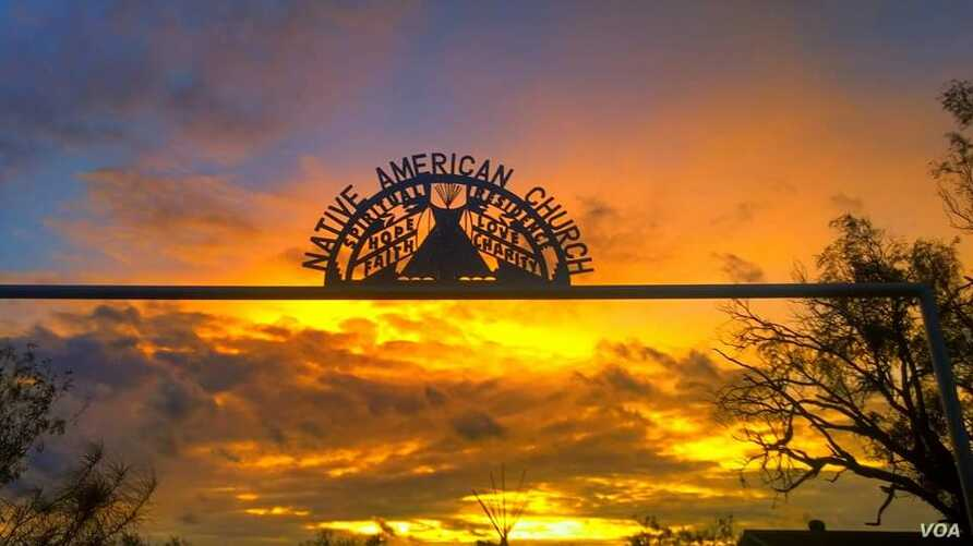The sun sets over the gateway of peyotera Amada Cardenas's house in Mirando City, Texas. Ironwork reflects core Native American Church values of faith, hope, love and charity.