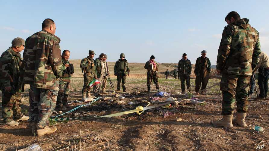Kurdish Peshmerga forces inspect a site in Hardan village in northern Iraq, Dec. 22, 2014, where Islamic State group fighters allegedly executed people from the Yazidi sect captured when they swept through the area in August.