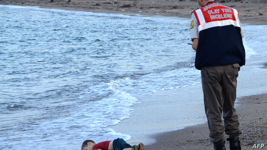 A Turkish police officer stands next to a migrant child's dead body (Aylan Shenu) off the shores in Bodrum, southern Turkey, on September 2, 2015 after a boat carrying refugees sank while reaching the Greek island of Kos.