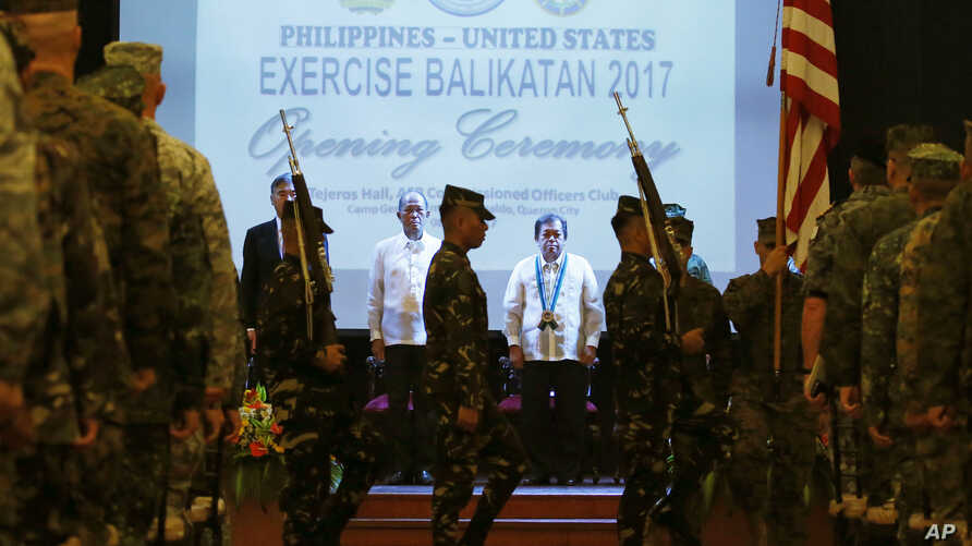 From left to right,  U.S. Ambassador to the Philippines Sung Kim, Philippines Defense Chief Delfin Lorenzana, Undersecretary of Foreign Affairs Ariel Abadilla, stand at attention during the entry of colors at the opening ceremony for this year's join