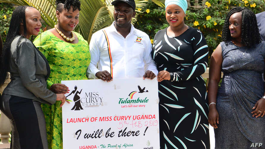 Uganda's minister for Tourism Godfrey Kiwanda (C) poses next to participants during the launch of the Miss Curvy beauty contest in capital Kampala, Feb. 5, 2019.