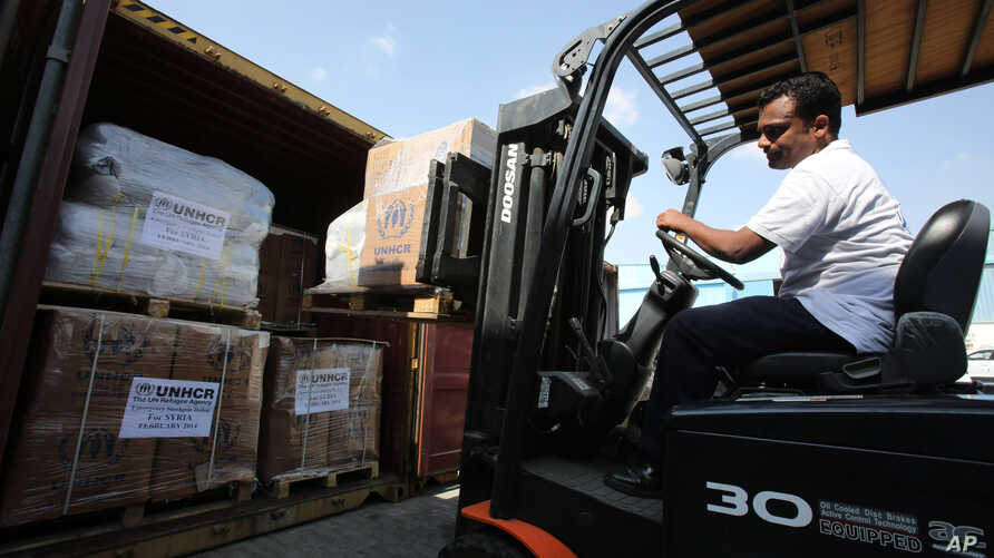 A lift truck driver offloads aid materials for Syria at the UNHCR warehouses in Dubai, part of the International Humanitarian City (IHC), the largest global stockpile for the UNHCR in Dubai, United Arab Emirates, Feb. 20, 2014.