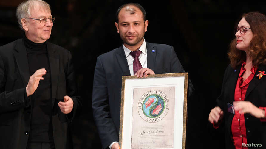 Raed al-Saleh (C), head of the Syria Civil Defense 'White Helmets', receives the Right Livelihood Award prize from Jakob von Uexkull (L), the founder of the award, during a ceremony at the Vasa Museum in Stockholm, Sweden, Nov. 25, 2016.