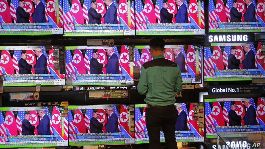 A man watches TV screens showing U.S. President Donald Trump, right, meeting with North Korean leader Kim Jong Un in Singapore, during a news program In Hong Kong, June 12, 2018.