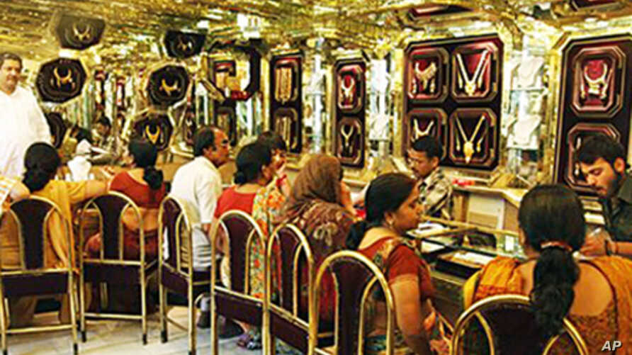 Customers look at gold jewelry at a shop on the occasion of a Hindu festival 'Akshay Tritiya' in Allahabad, India, 16 May 2010