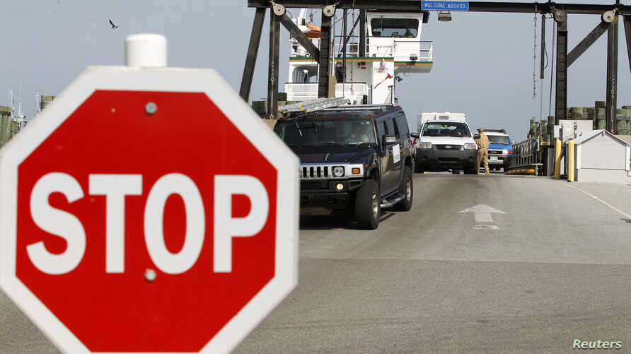 FILE - People arrive at Cape Hatteras ferry terminal in North Carolina, Aug. 25, 2011. The ferry is the only off Ocracoke Island, one of two island off the North Carolina coast where tourists have been evacuated because of a power outage.