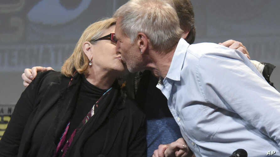 "FILE - Carrie Fisher, left, and Harrison Ford kiss at the Lucasfilm's ""Star Wars: The Force Awakens"" panel on day 2 of Comic-Con International in San Diego, Calif."
