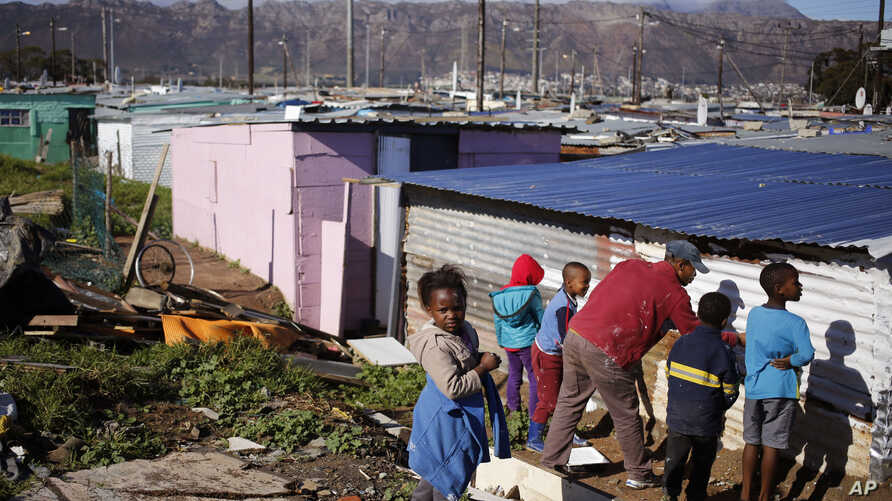 Children paint a shack with white fire retardant paint as part of their contribution to International Nelson Mandela day celebrating former South African president Mandela birth day in the township of Nomzamo, South Africa, July 18, 2015.