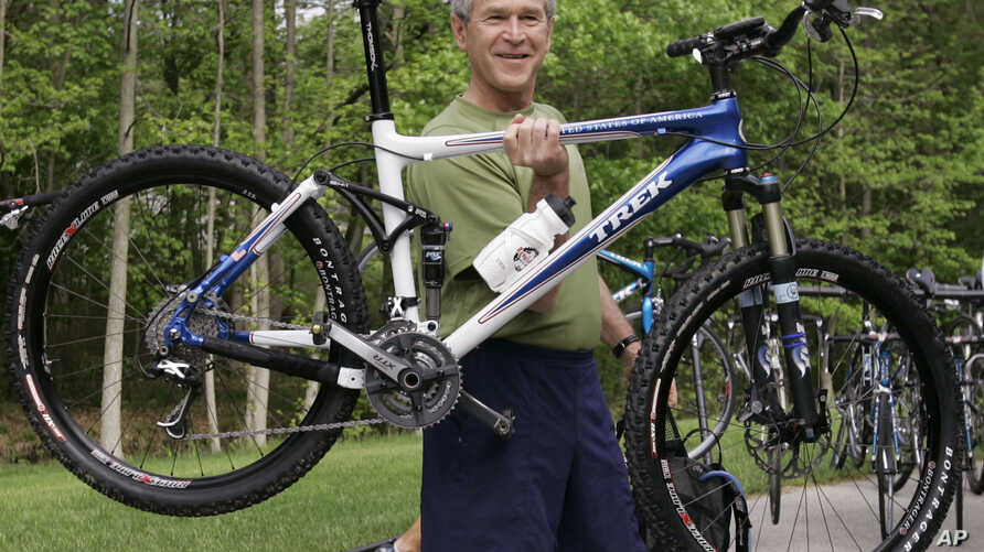 FILE - President George W. Bush lifts his bicycle before taking a mountain bike ride in Beltsville, Md.