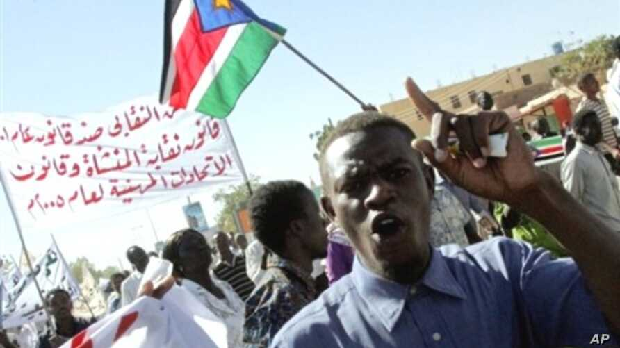 A Sudanese opposition supporter shouts slogans as protesters wave the flag of Sudan People's Liberation Movement (SPLM) during a demonstration against the government in Khartoum, 07 Dec 2009
