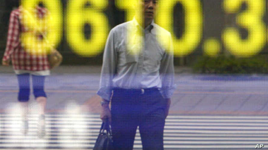 A man is reflected on an electric board showing the Nikkei 225 index in Tokyo, Japan, August 3, 2011