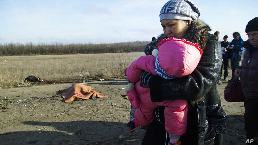 A woman with her child and others pass body of the man, who died in a land mine explosion near a frontline crossing to Ukrainian government controlled territory, in the war conflict-hit Donetsk region, near Donetsk, eastern Ukraine, Feb. 10, 2015.
