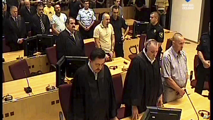 A TV image provided by the Bosnian war crimes court showing former Bosnian Serb soldiers Franc Kos, first row right, Stanko Kojic second row center, Vlastimir Golijan third row center, and Zoran Goronja, fourth row right, during the pronouncement of