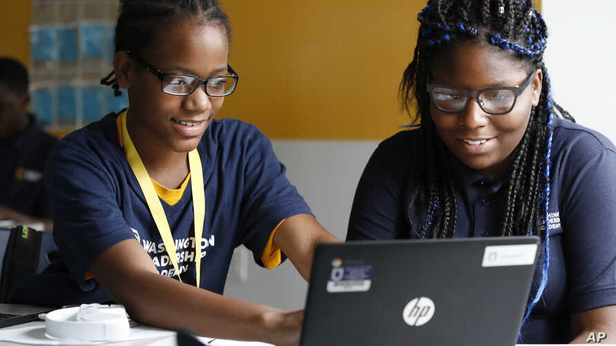 """Jahiem Johnson, 13, left, helps classmate Kamya Saunders, 13, as they work on an English passage during class at the Washington Leadership Academy in Washington, Aug. 23, 2017. The school utilizes """"personalized learning."""""""