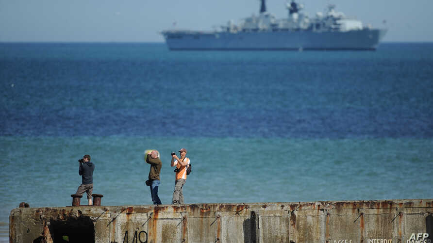 """FILE - People take pictures on a remain of the World War II """"Mulberry"""" artificial harbour as a warship is anchored in the English Channel in Arromanches-les-Bains, Normandy."""