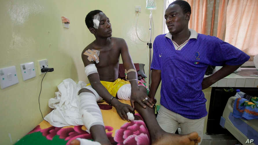 A victim of latest bomb explosion at a bus park gets a visit from his brother at the Asokoro hospital in Abuja, Nigeria, April 16, 2014.