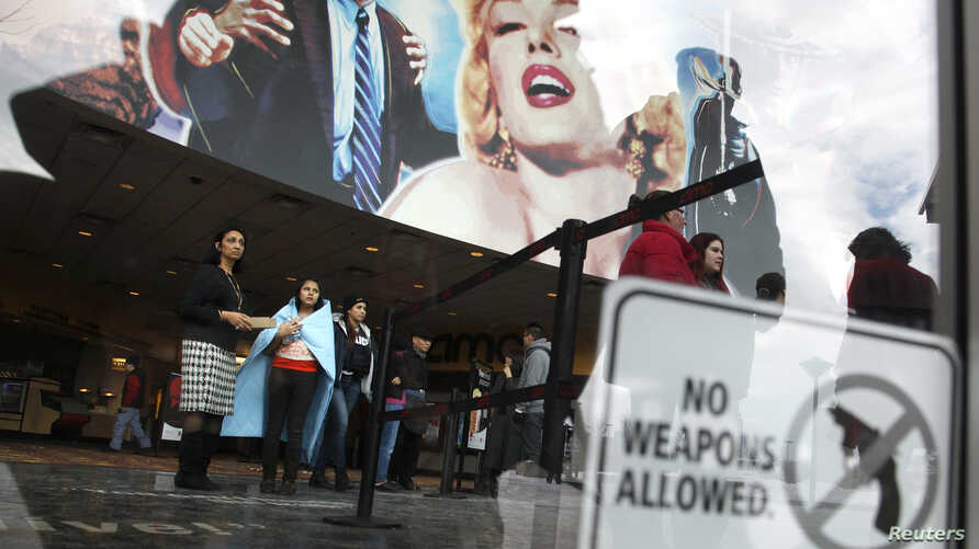 FILE - Mall employees and patrons are held in a theater lobby as law enforcement officials speak with them as potential witnesses in a shooting at the Mall of Columbia shopping center in Columbia, Maryland, January 25, 2014.