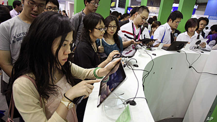 Visitors test new tablets at the Computex computer expo in Taipei,Taiwan, June 2, 2011.