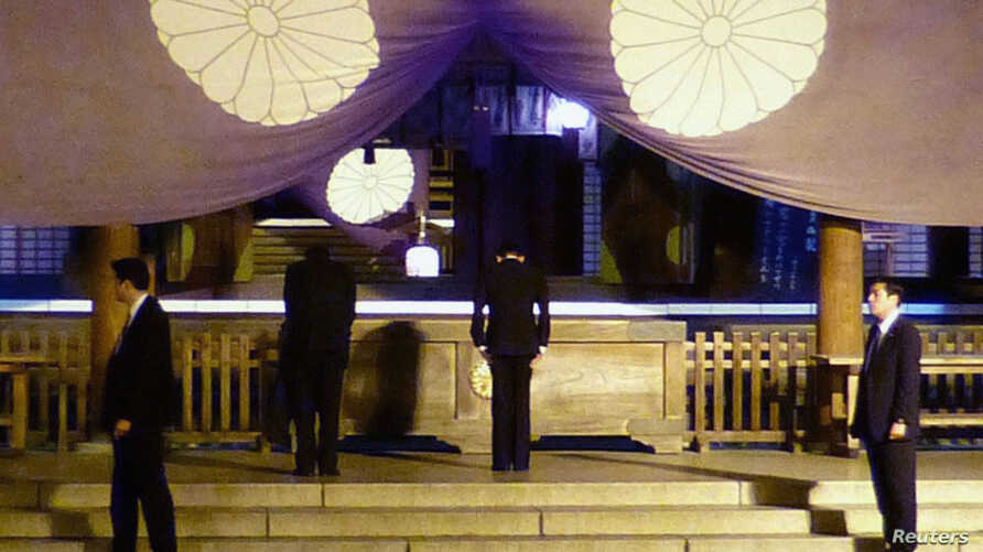Japan's Finance Minister Taro Aso (2nd R) bows as he visits the Yasukuni Shrine in Tokyo, in this photo provided by Kyodo, April 21, 2013.
