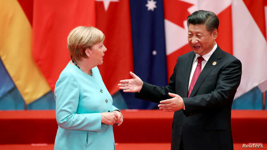FILE - Chinese President Xi Jinping talks with German Chancellor Angela Merkel as they pose for a group picture during the G20 Summit in Hangzhou, Zhejiang province, China September 4, 2016.