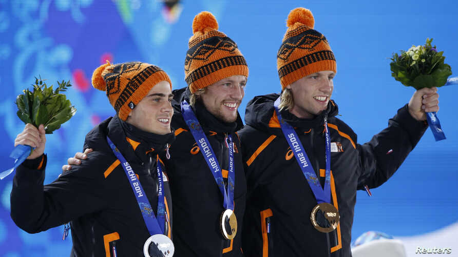 Gold medallist Michel Mulder of the Netherlands (C) poses with his compatriots silver medallist Jan Smeekens and bronze medallist Ronald Mulder (R), during the victory ceremony for the men's speed skating 500m race at the 2014 Sochi Winter Olympics,