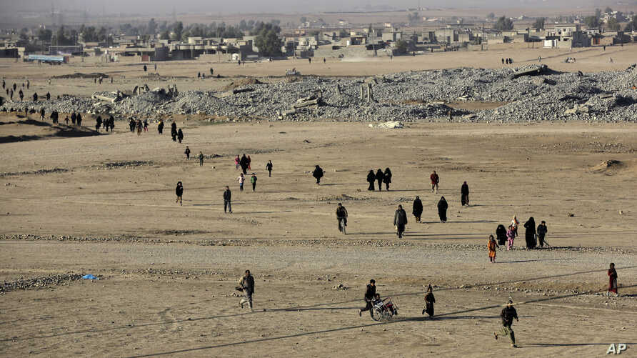 Iraqi citizens who fled the fighting between the Islamic State militants and the Iraqi forces, walk in front of destroyed houses on their way to receive aid supplies and clothes, in the Samah front line neighborhood, in Mosul, Iraq, Nov. 28, 2016. Th