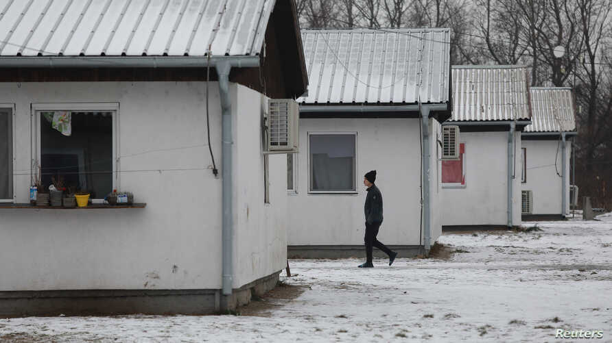 A man walks through the camp for refugees and migrants in the Belgrade suburb of Krnjaca, Serbia, Jan. 16, 2018.