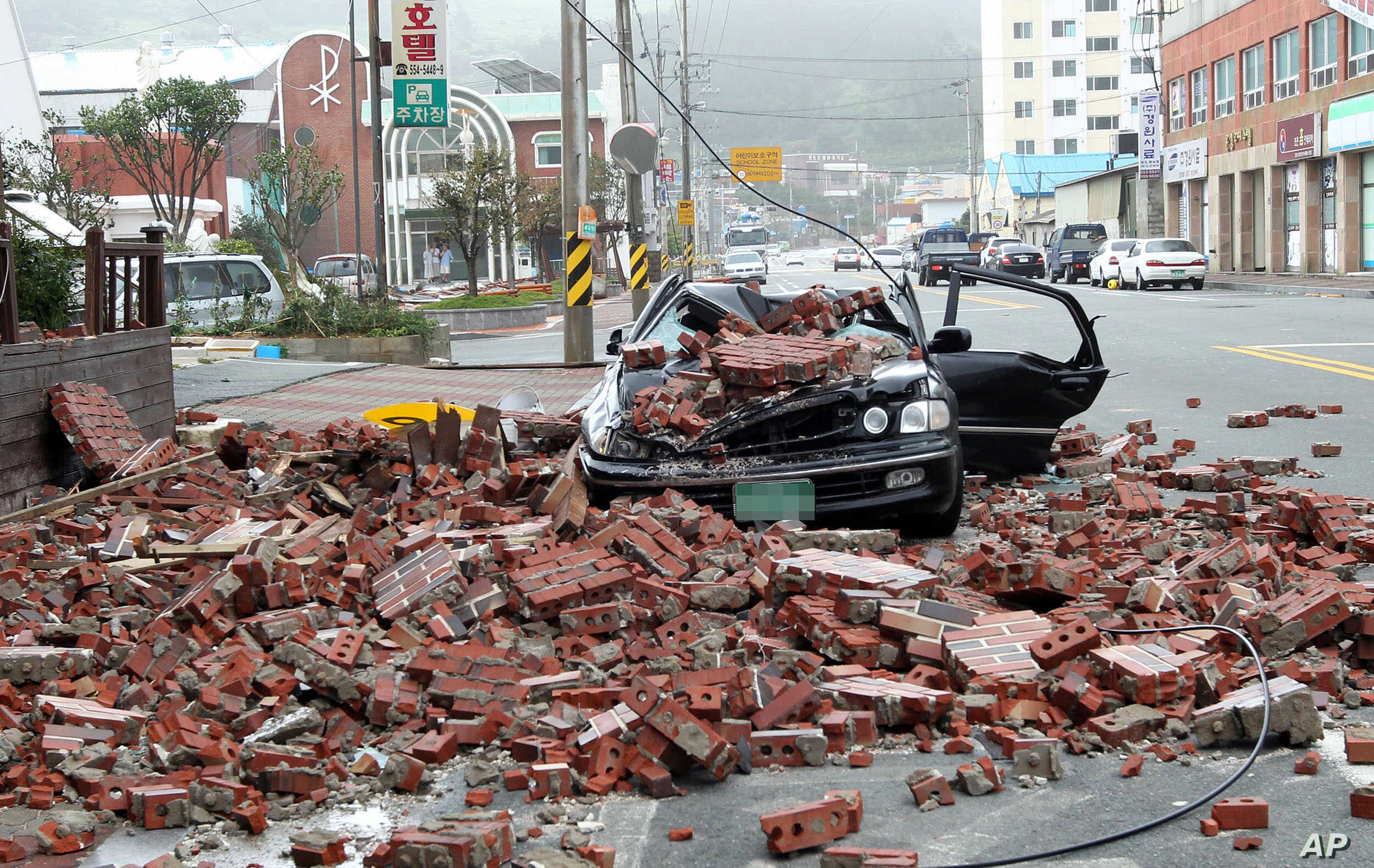 A vehicle damaged by fallen bricks from a building as Typhoon Bolaven brings heavy downpours and winds to Wando, South Korea, August 28, 2012.