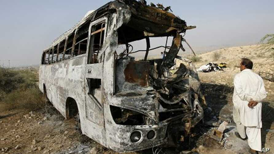 A man walks past the wreckage of a bus which was burned after it collided with an oil tanker in Nooriabad, in Pakistan's Sindh province 23 Jan 2011.
