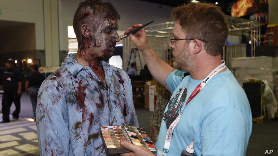 """A zombie has his makeup done at AMC's """"Walking Dead"""" booth before Preview Night at Comic-Con International, held at the San Diego Convention Center, July 8, 2015."""