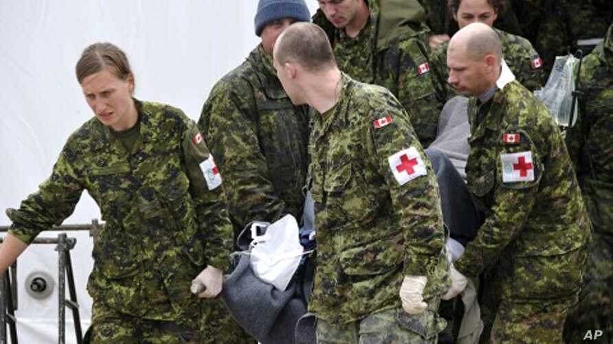 Canadian Forces medical members carry a stretcher out of the medical center to a vehicle with one of the three survivors from the First Air flight 6560 plane crash in Resolute Bay, Nunavut, August 21, 2011