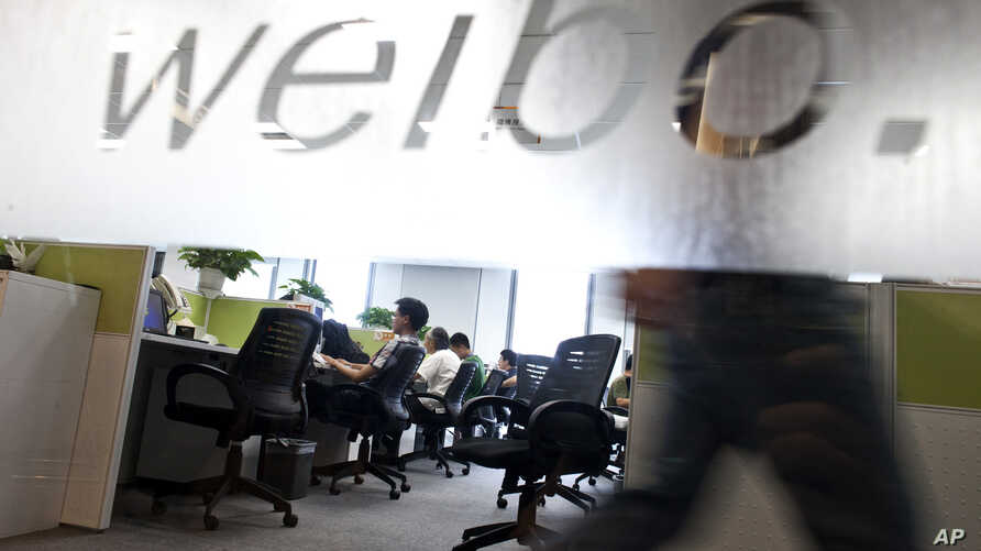 FILE - Employees work at their desks at a Sina Weibo office in Beijing.