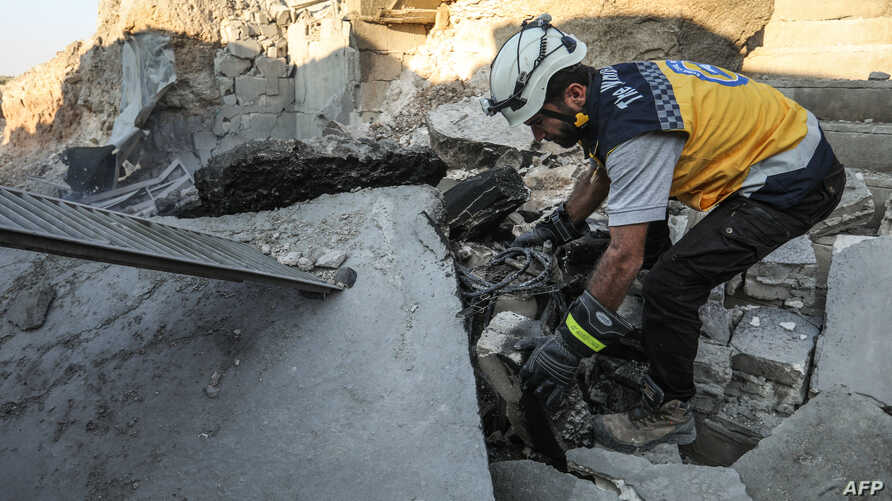 A member of the Syrian Civil Defense, also known as the White Helmets, searches through the wreckage of their center, which was destroyed by government forces in the town of al-Tamana on the southern edges of the rebel-held Idlib province, Sept. 6, 2...