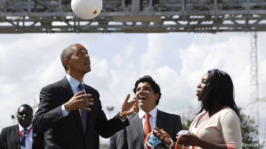 """FILE - U.S. President Barack Obama bounces a soccer ball with his head at Ubungo Power Plant in Dar es Salaam, July 2, 2013. The ball, called a """"soccket ball,"""" has internal electronics that allow it to generate and store electricity that can power sm"""