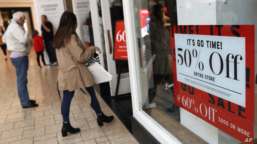 FILE - Discount signs stand in the window of a clothing store as last-minute shoppers finish up their Christmas gift lists at the Cherry Creek Mall in Denver, Dec. 24, 2018. Americans buoyed by a strong economy pushed holiday sales growth to a six-ye