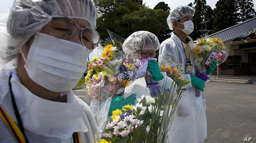 Mourners in protective suits hold flowers at a memorial ceremony for residents from the town of Okuma, inside the contaminated exclusion zone near the crippled Fukushima Dai-Ichi nuclear power plant, July 24, 2011. (AP)