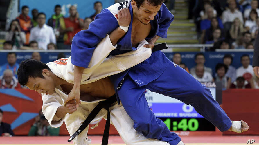 FILE - South Korea's Cho Jun-ho, left, throws Spain's Sugoi Uriarte in the men's 66 kg bronze medal match in during their judo competition at the 2012 Summer Olympics, Sunday, July 29, 2012, in London.