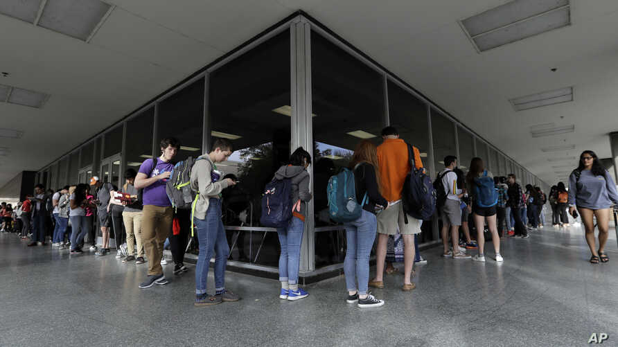 A line of mostly students wait to vote at a Texas primary election polling site on the University of Texas campus, March 6, 2018, in Austin.