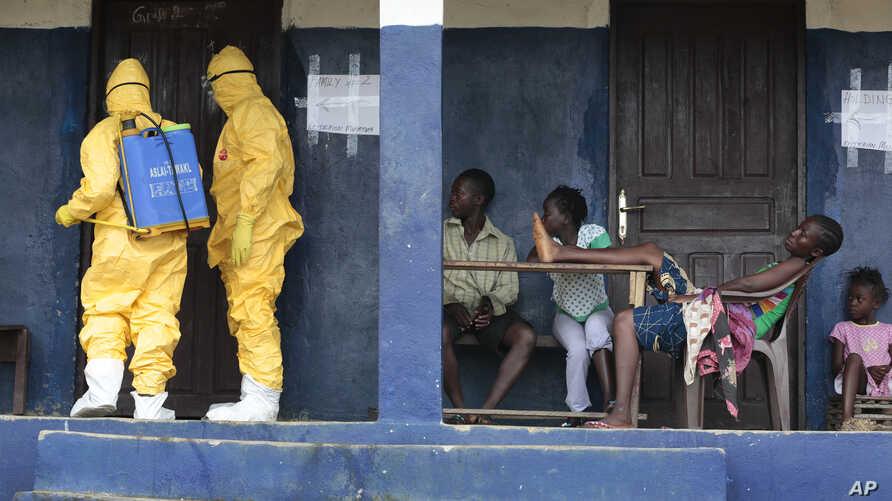 Residents of the village of Freeman Reserve watch members of District 13 ambulance service disinfect a room as they pick up six suspected Ebola sufferers that had been quarantined, Sept. 30, 2014.