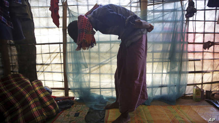 In this Nov. 27, 2017, photo, Mohamed Yaha, 18, demonstrates what he saw when soldiers bound the hands of dozens of men behind their backs with nylon rope and blindfolded them with scarves taken from the women when they massacred his village in Myanm
